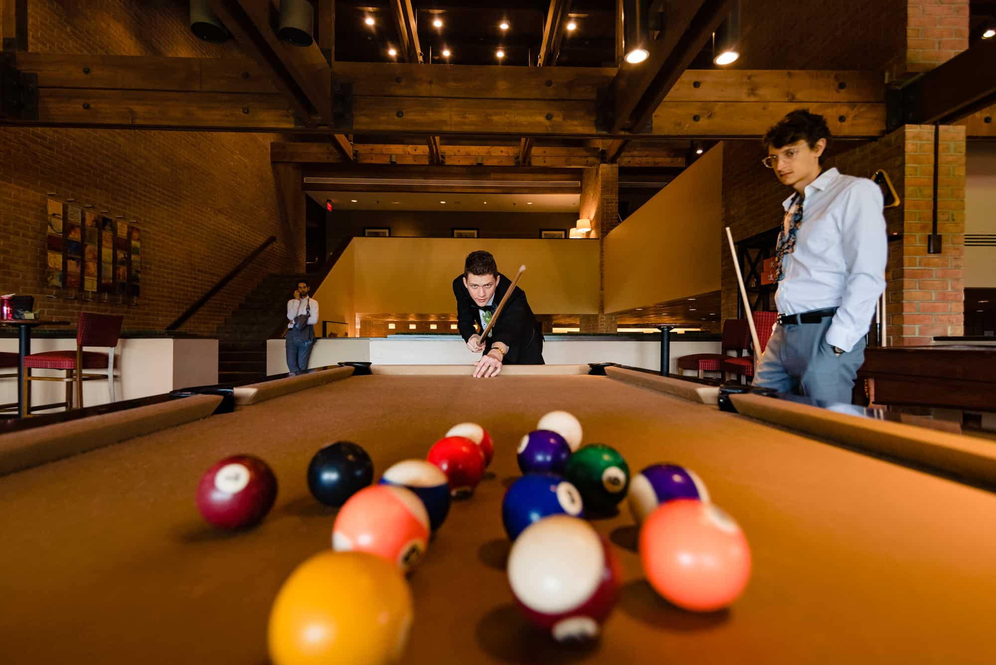 groom playing billiards before his Morris Arboretum Wedding