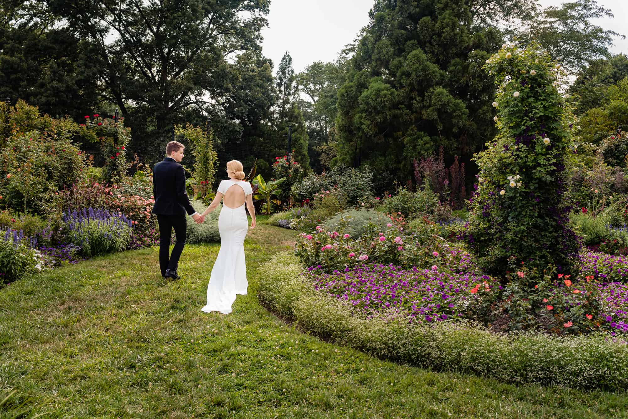 bride and groom in a beautiful field of flowers walking while holding hands at their Morris Arboretum Wedding