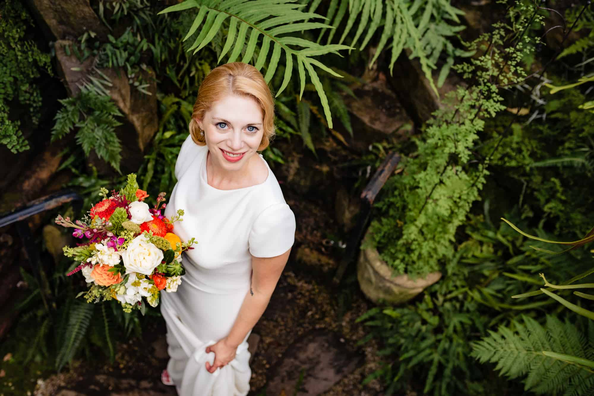 bride posing while holding her flowers at her Morris Arboretum Wedding