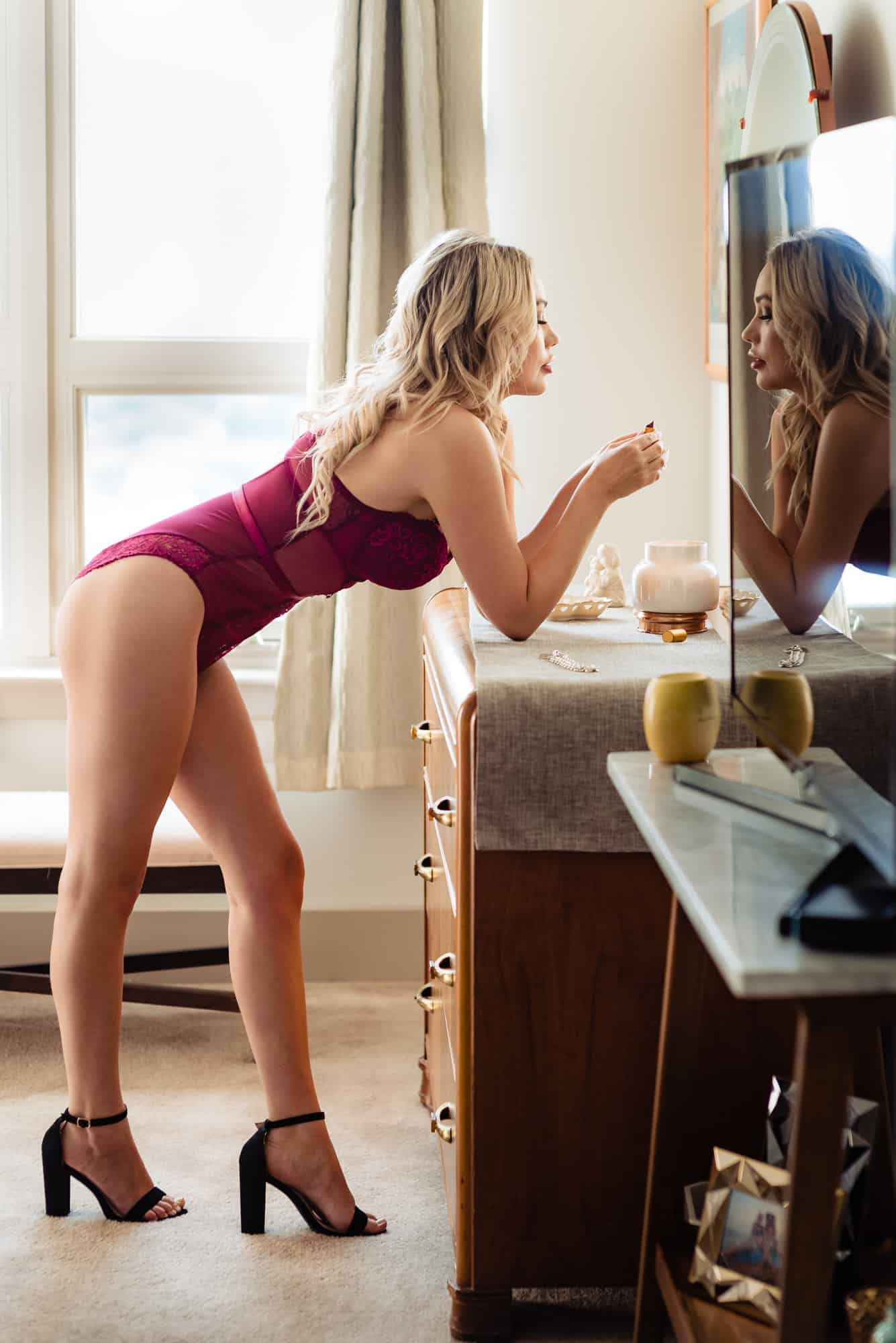 boudoir photo of woman in red lingerie looking in mirror