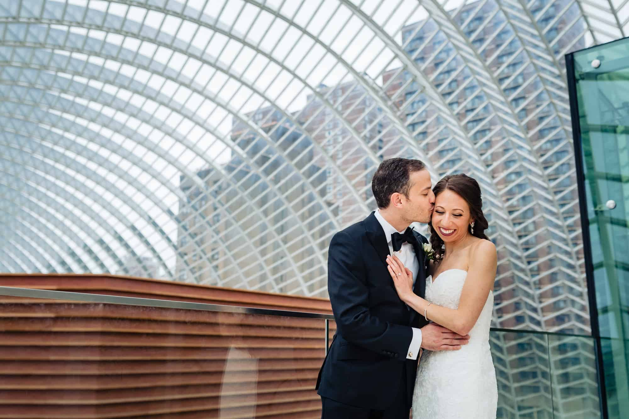 groom kissing bride on cheek at the Kimmel Center for the Performing Arts