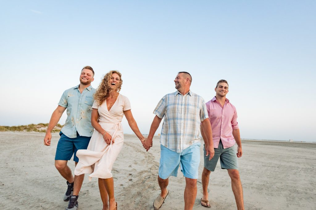 lifestyle photo of family walking together on a beach