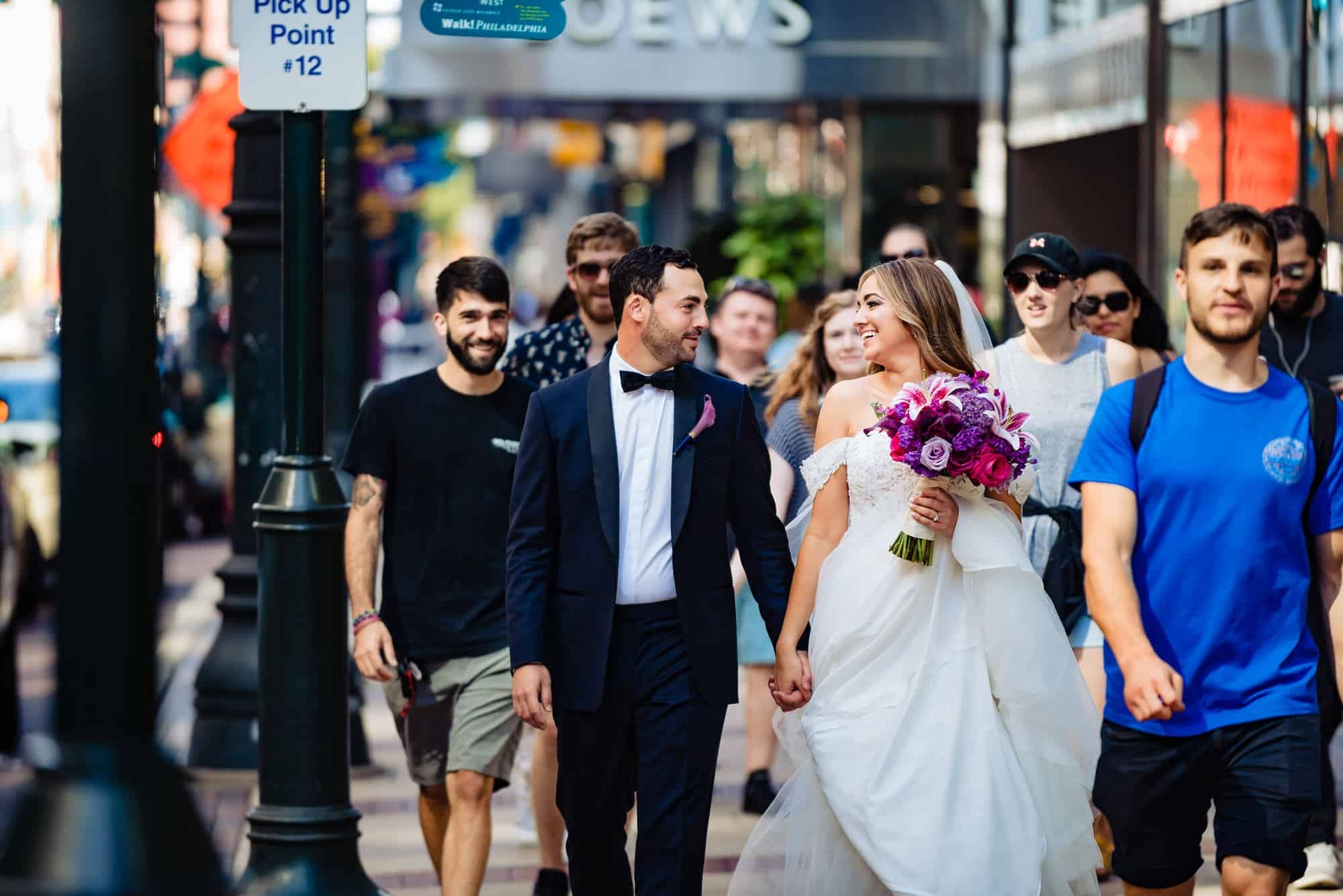 bride and groom walking on crowded street before their Philadelphia Wedding