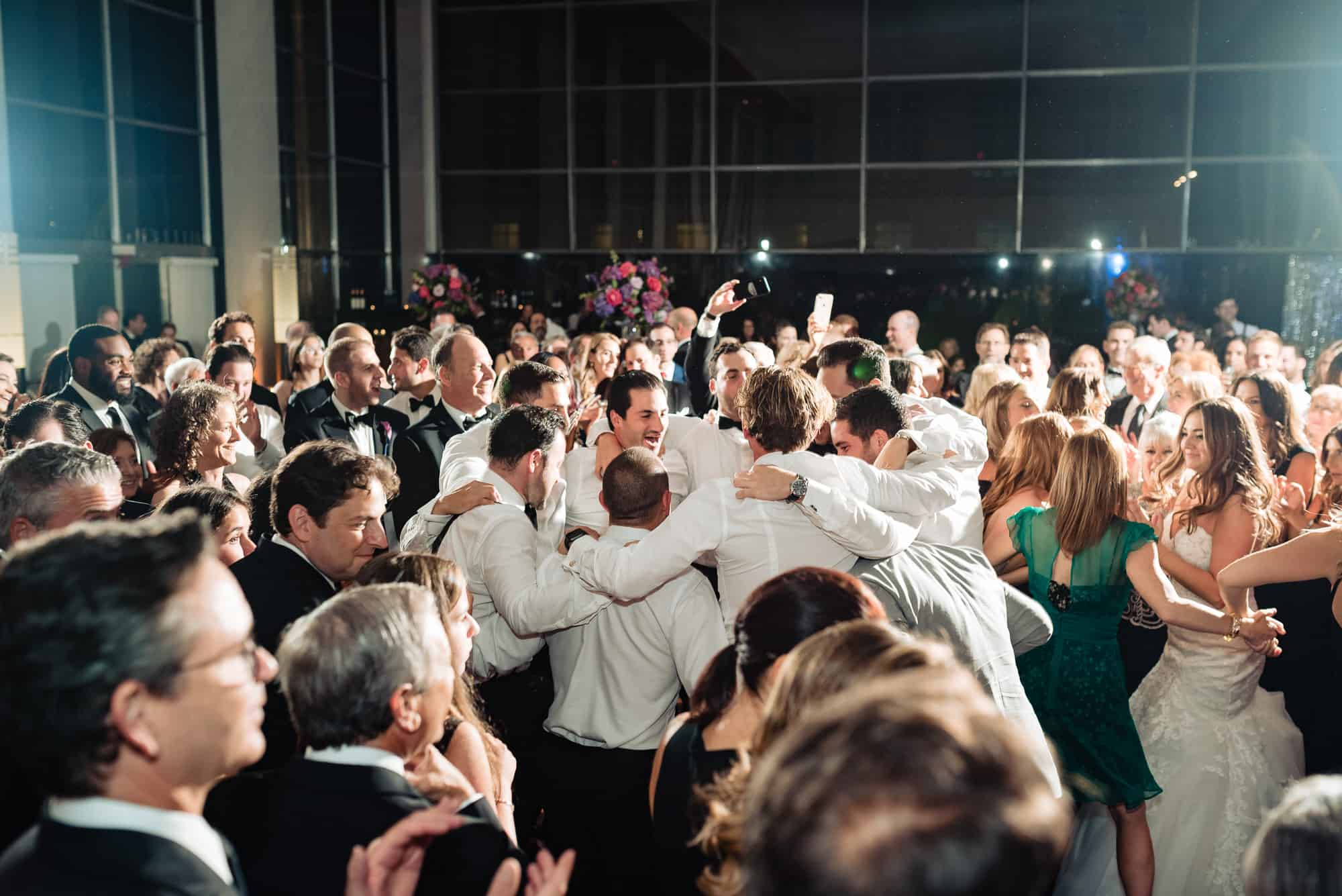 image of groom and groomsman in a circle at a Loews Philadelphia Wedding reception