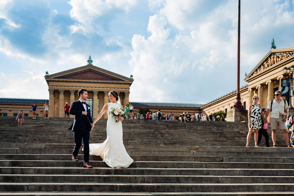 bride and groom walking down Philly Art Museum steps during their Hilton Penn's Landing Wedding