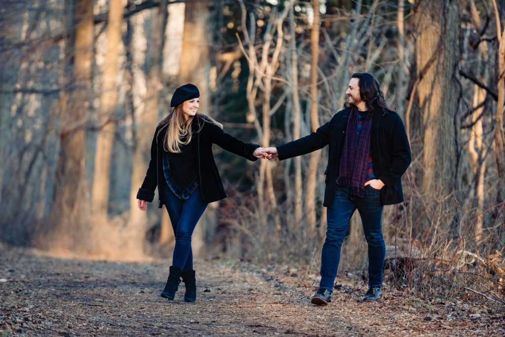 couple holding hands and walking through the woods in Lambertville NJ