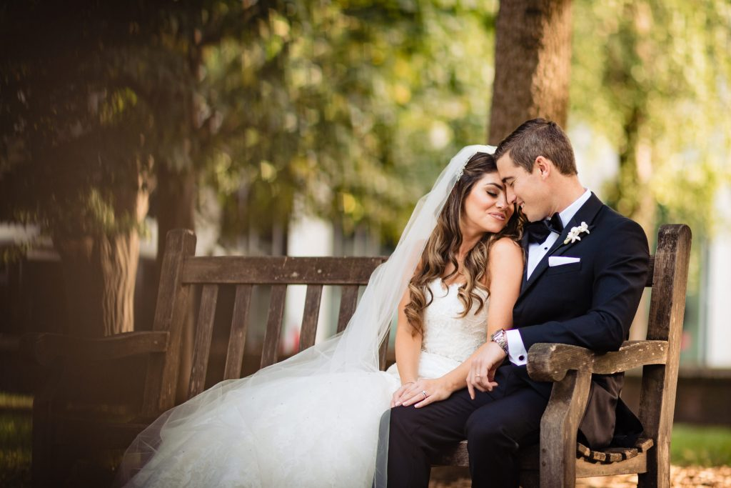 bride and groom sitting on park bench before their Union Trust Ballroom wedding reception