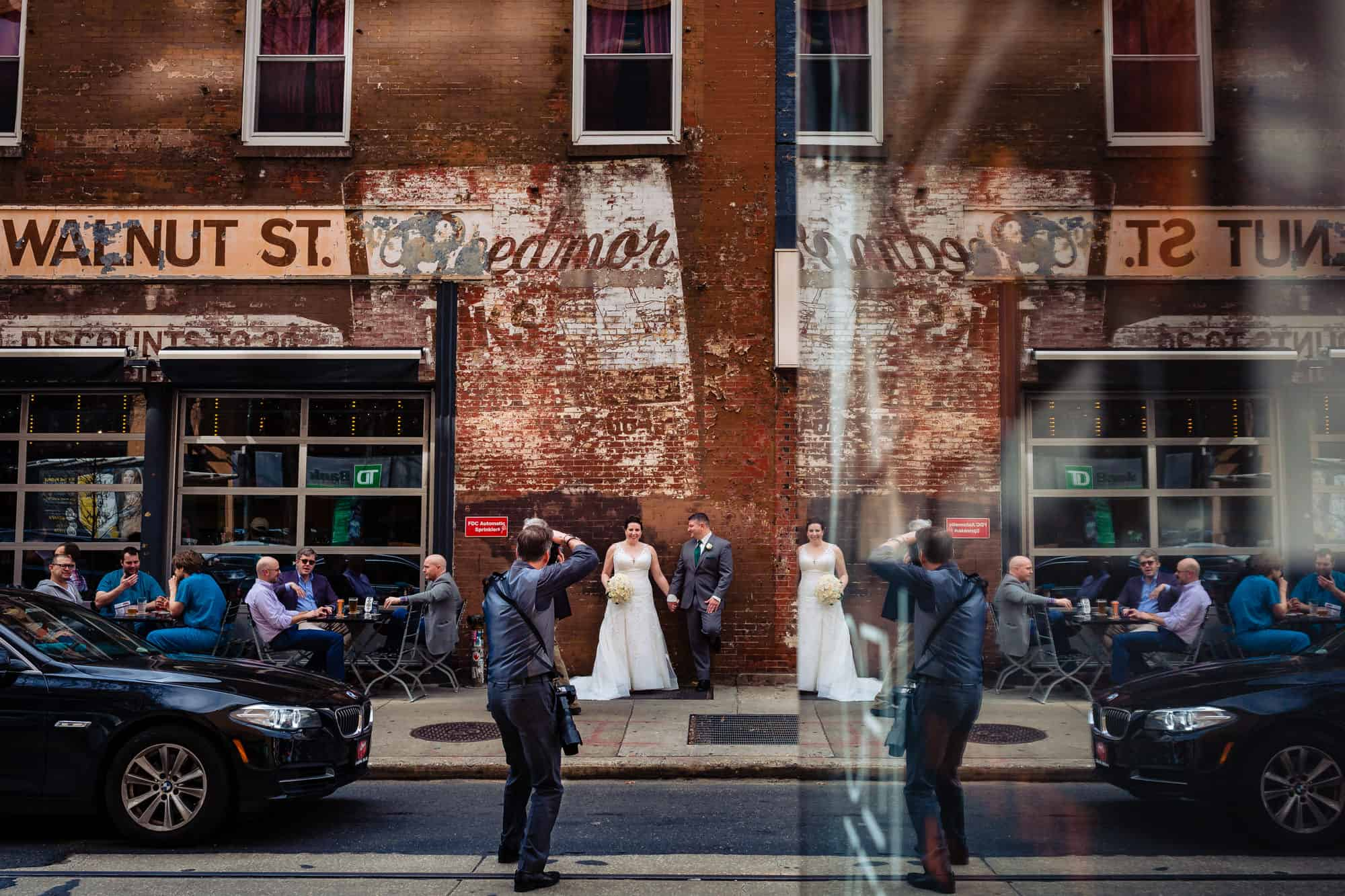 photographer in a large city taking a photo of a bride and groom