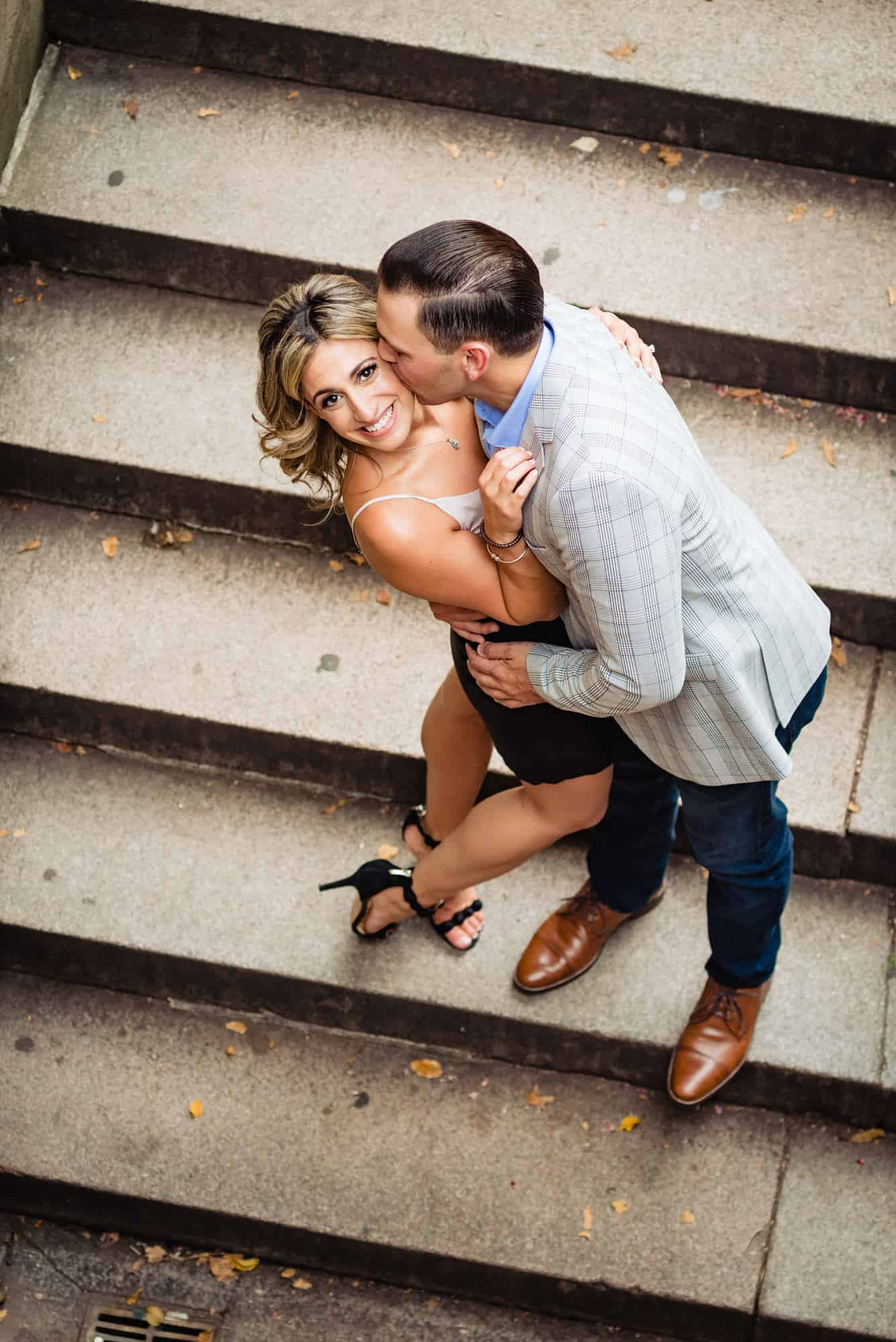 couple on steps embracing while female looks at camera in central park