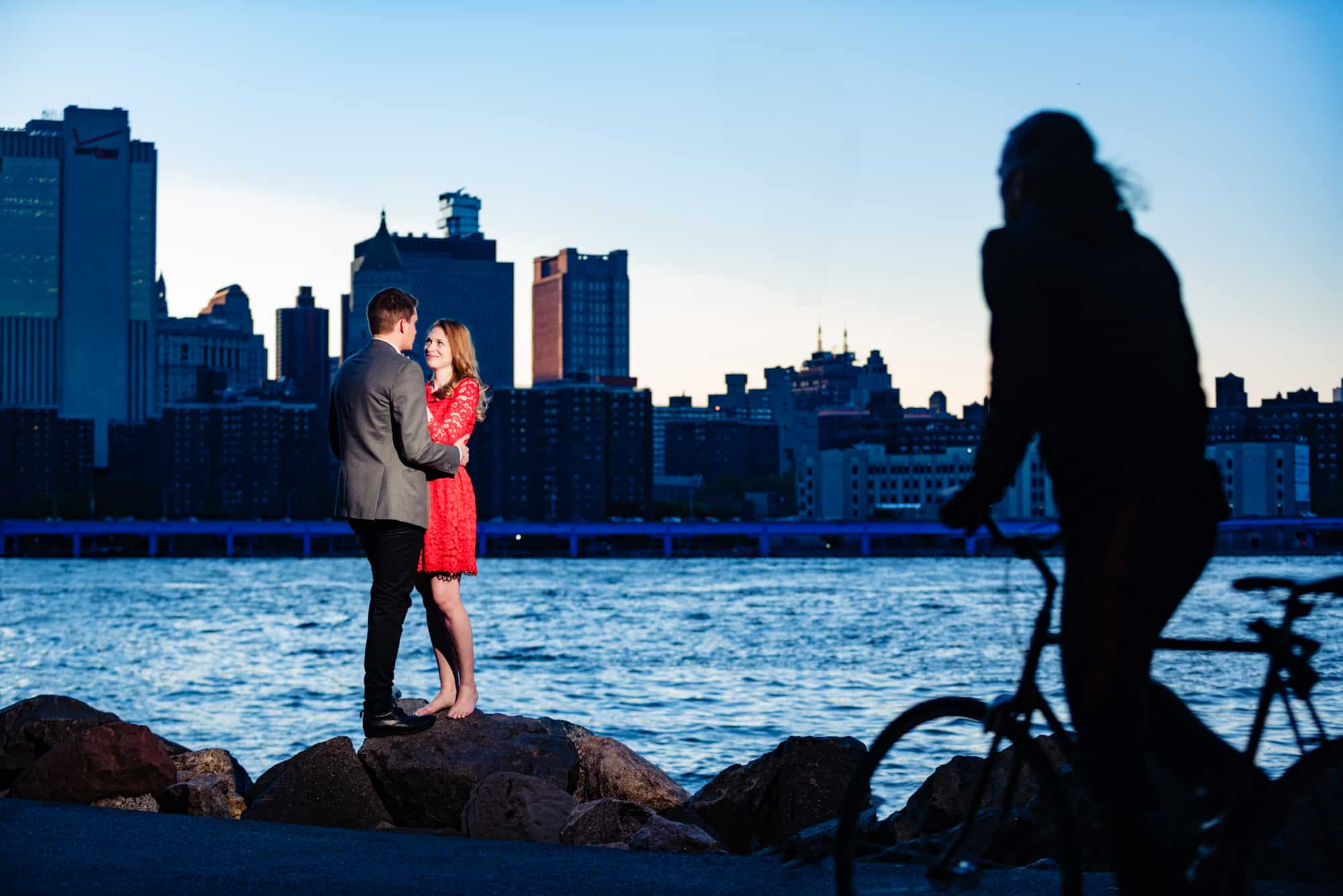 couple embracing while standing on rocks next to a river in DUMBO Brooklyn