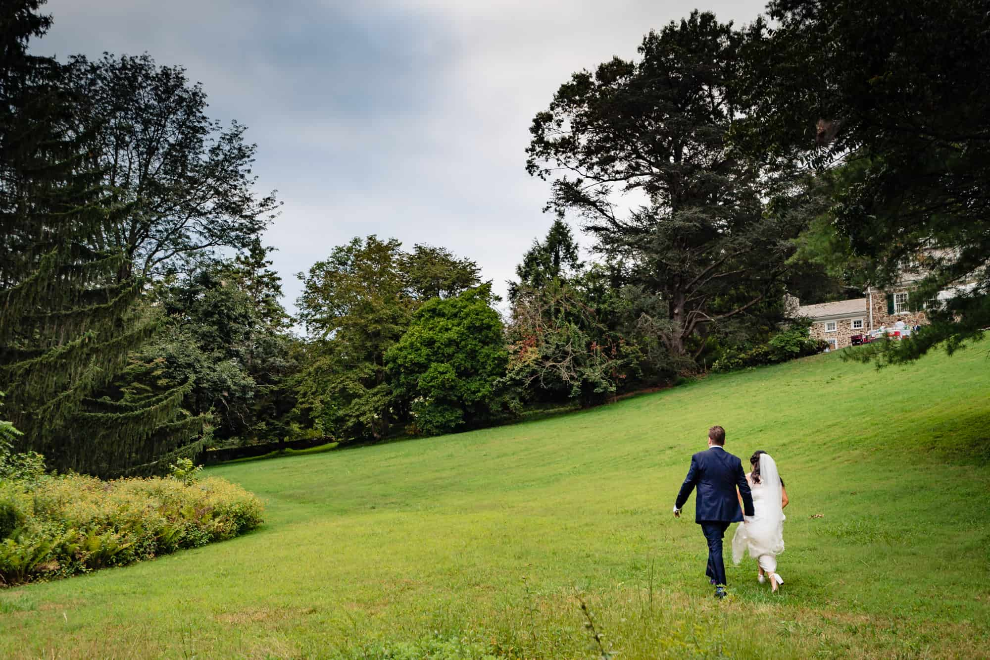 bride and groom walking hand in hand at the Welkinweir Estate