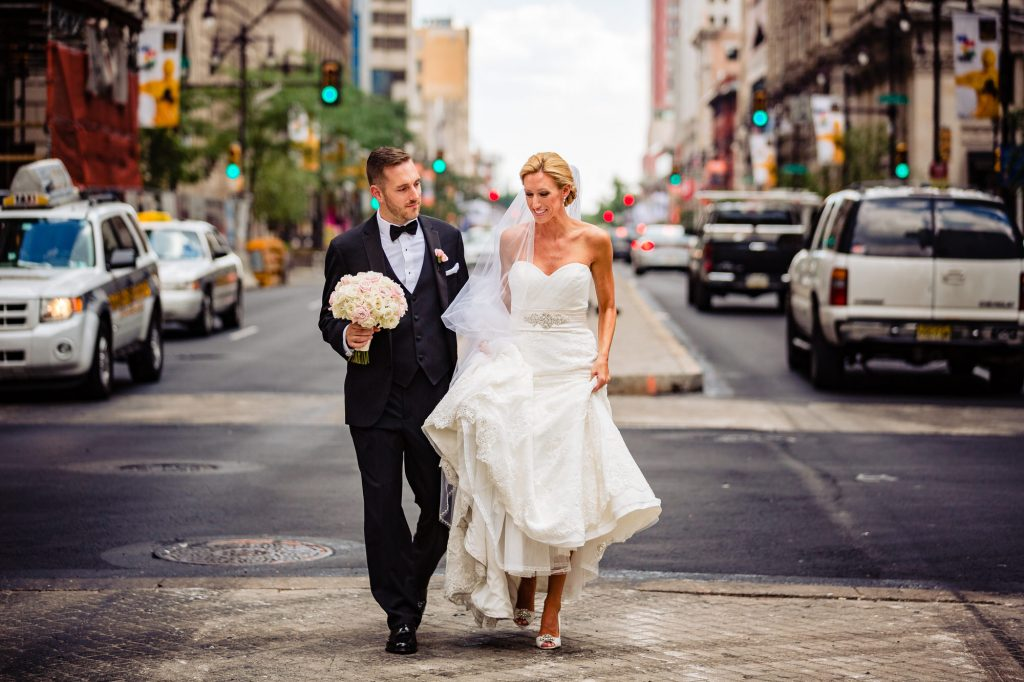 bride and grrom walking on a city steet during their city wedding
