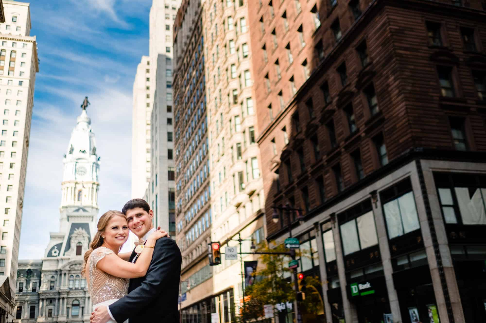bride and groom in front of philadelphia city hall before their cescaphe waterworks wedding