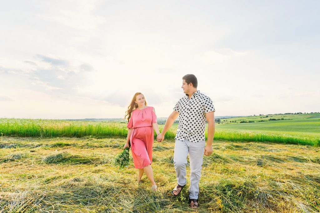 pregnant couple walking hand in hand during their maternity photo session
