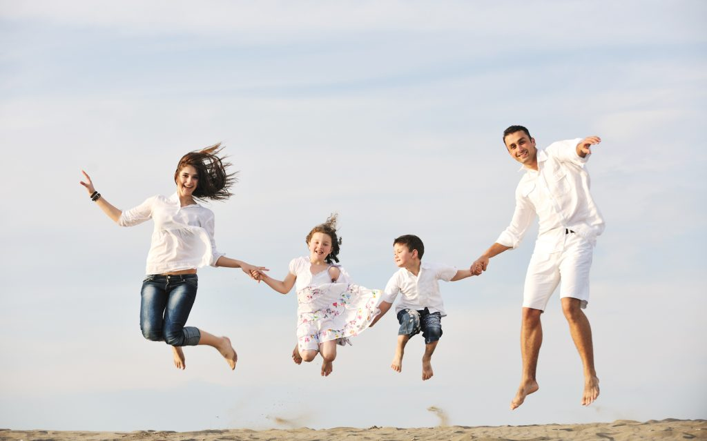a family jumping in a posed image at the beach