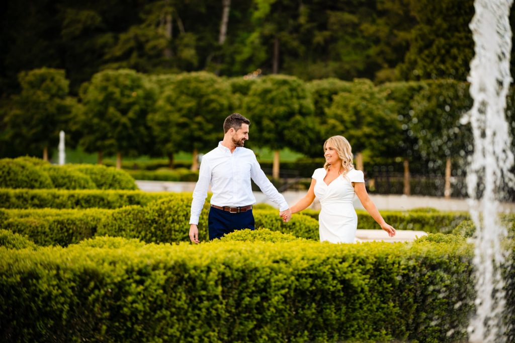 couple holding hands while walking during their engagement session at Longwood Gardens